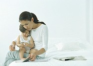 Woman sitting on edge of bed with little girl on lap, looking down at agenda (thumbnail)
