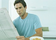 Young man sitting at table with bowl of cereal holding financial page of newspaper