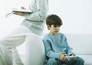 Man sitting on arm of sofa writing in agenda, boy sitting on sofa with joy stick