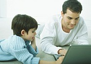 Man and little boy lying on floor on stomachs, working on laptop