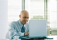 Businessman using laptop, smiling