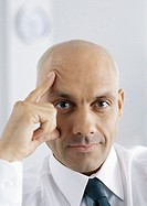 Businessman with fingers on face and forehead, portrait