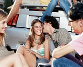 Group of Teenagers Sit Laughing at the Rear Bumper of a Car