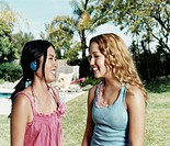 Two Teenage Girls Stand Laughing Face-to-Face in a Garden