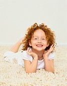 Young Girl Lying on a Rug Smiling and Leaning on Her Elbows