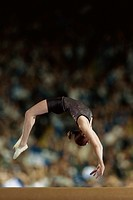Female gymnast performing on the balance beam in front of a large crowd (thumbnail)