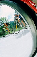 Cyclists viewed through wheel