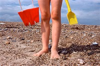 Child on beach with bucket and spade (thumbnail)