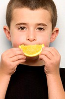 Boy holding orange segment to mouth