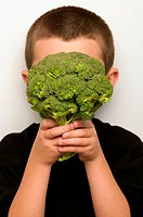 Boy covering face with broccoli (thumbnail)