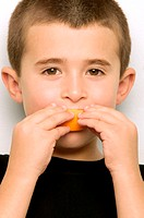 Boy eating an orange segment