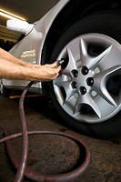 A mechanics hand as he adds air to a car tire