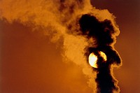 Industrial air pollution. Smoke rising from a chimney stack obscures the setting Sun over an asphalt plant in Canada.