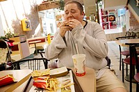 Obese man eating a burger in a McDonald´s restaurant.