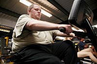 Obese man exercising. Obese man using a rowing machine at a gym.