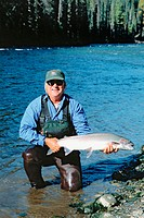 Fly fisherman holding wild steelhead, Babine river. British Columbia. Canada