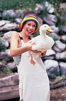 woman with a white dress and a coloured hat carring a goose on her arms