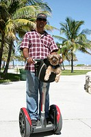 Segway personal transporter, man with small dog. Lummus Park, Ocean Drive. South Beach. Miami Beach. Florida. USA.