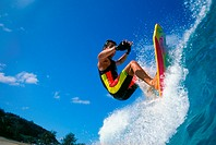 Hawaii, Close-up of man standing on bodyboard towards camera, rips top of lip