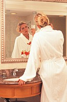 Lady in white robe, putting on makeup in resort bathroom