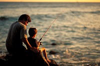 Local family, father and son fishing at sunset on rocks by ocean