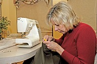 Adult female relaxes while sewing for pleasure
