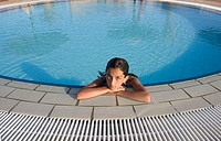 Girl (13 years) relaxing at edge of circular swimming pool. El Quesir. Egypt