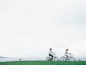 Young man and woman bicycling on grass with sea and overcast sky in background