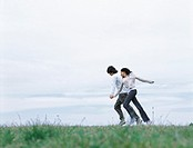 Young man and woman holding hands and running on grass