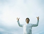 Young man with hands up in air in front of overcast sky