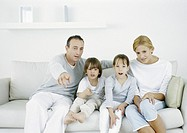 Parents with sitting on sofa with daughter and son, father pointing straight ahead