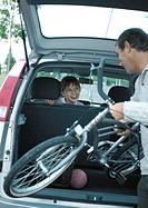 Man putting bicycle into trunk of car, girl in car turning around smiling at man