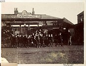 A snapshot photograph of a group of children outside a pub or brewery, taken by an unknown photographer in about 1895.  Originally a shooting term, th...