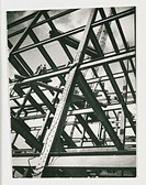 A photograph of two men standing amongst the metal girders of a building under construction, taken by an unknown photographer in 1936.