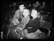 A photograph of two children with their mother eagerly watching a Bertram Mills Circus dress rehearsal at Olympia, London, taken by Malindine for the ...