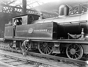 A Lancashire & Yorkshire Railway worker examining a 2-4-0 locomotive number 1045 at Manchester Victoria station, 23 August 1922.  Locomotives needed r...