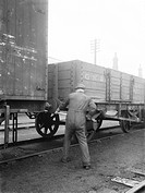 Worker risking injury by using a pole to couple two wagons with his hand between the buffers, Doncaster works, January 1930.   This photograph was tak...
