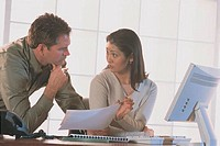 Woman and man talking at computer