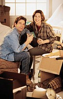 Couple unpacking boxes, enjoying a glass of wine, portrait