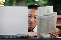 Man with laptop and newspaper