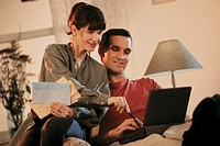 Couple at home with bills using laptop computer