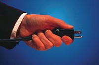 Businessman holding electric plug.