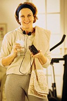 Woman in exercise room holding a glass of ice water and portable tape player, portrait