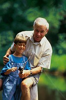 Grandfather teaching boy to fish