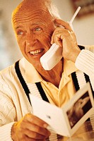 Elderly man talking on telephone, holding a greeting card