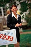 Realtor in front of house just sold, portrait