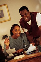 Young couple paying bills, portrait