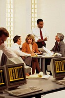 Four business people at table, meeting. One man looking at computer in foreground
