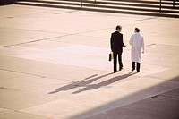 Doctor and businessman walking and talking