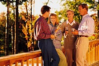 Group of four people talking outdoors on deck